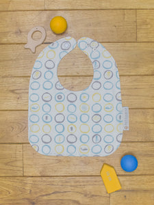 An organic Poco Bambino bib. The print is blue, yellow and grey with a sea creatures design.