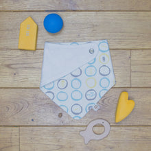 Load image into Gallery viewer, An organic Poco Bambino dribble bib. The print is white, blue, yellow and grey with sea creatures design. One corner is folded up to show the organic cotton and bamboo terry reverse