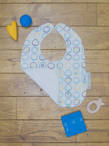 An organic Poco Bambino bib. The print is blue, yellow and grey with a sea creatures design. One corner is folded up to show the organic cotton and bamboo terry reverse