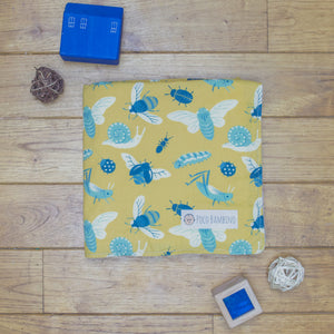 An organic Poco Bambino blanket. The print is mustard with blue insects and bugs.