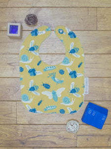 An organic Poco Bambino bib. The print is mustard with a blue bugs and insects design.