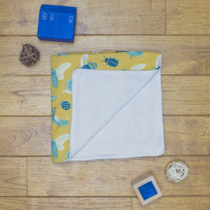 An organic Poco Bambino blanket. The print is mustard with blue insects and bugs. One corner is folded up to show the organic cotton and bamboo fleece reverse