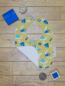 An organic Poco Bambino bib. The print is mustard with a blue bugs and insects design. One corner is folded up to show the organic cotton and bamboo terry reverse