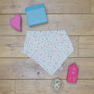 An organic Poco Bambino dribble bib. The print is a multicoloured spots design.