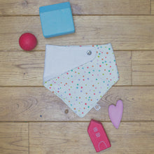Load image into Gallery viewer, An organic Poco Bambino dribble bib. The print is a multicoloured spots design. One corner is folded up to show the organic cotton and bamboo terry reverse