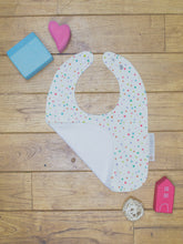 Load image into Gallery viewer, An organic Poco Bambino bib. The print is multicoloured spots design. One corner is folded up to show the organic cotton and bamboo terry reverse