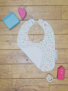 An organic Poco Bambino bib. The print is multicoloured spots design. One corner is folded up to show the organic cotton and bamboo terry reverse