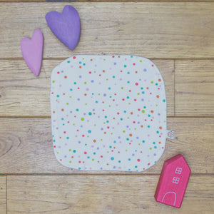 An Organic Poco Bambino reusable wash cloth / wipe in a multicoloured spots print.