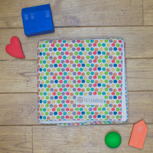 An organic Poco Bambino blanket. The print is a rainbow dots design.