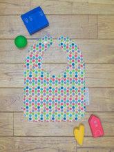 Load image into Gallery viewer, An organic Poco Bambino bib. The print is a rainbow dots design.