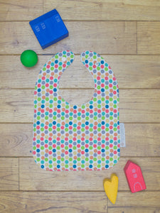 An organic Poco Bambino bib. The print is a rainbow dots design.