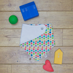 An organic Poco Bambino dribble bib. The print is a rainbow spots design. One corner is folded up to show the organic cotton and bamboo terry reverse