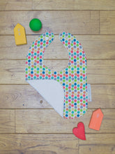 Load image into Gallery viewer, An organic Poco Bambino bib. The print is a rainbow dots design. One corner is folded up to show the organic cotton and bamboo terry reverse