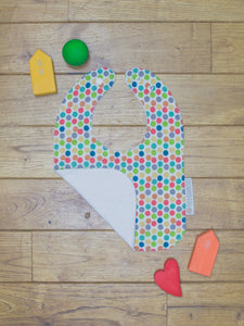 An organic Poco Bambino bib. The print is a rainbow dots design. One corner is folded up to show the organic cotton and bamboo terry reverse