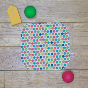 An Organic Poco Bambino reusable wash cloth / wipe in a rainbow dots print.