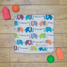 Load image into Gallery viewer, An organic Poco Bambino blanket. The print is a rainbow elephant parade design.