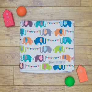 An organic Poco Bambino blanket. The print is a rainbow elephant parade design.