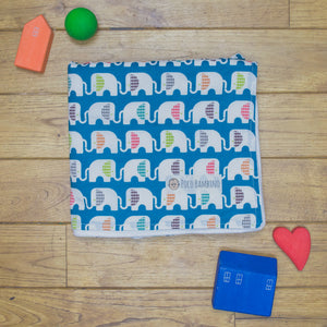 An organic Poco Bambino blanket. The print is blue with rainbow elephants.