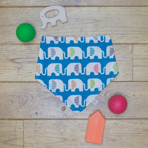 An organic Poco Bambino dribble bib. The print is blue with a rainbow elephant design.