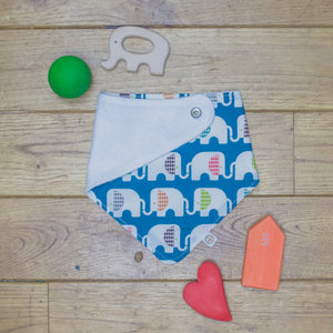 An organic Poco Bambino dribble bib. The print is blue with a rainbow elephant design. One corner is folded up to show the organic cotton and bamboo terry reverse