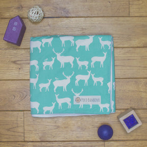 An organic Poco Bambino blanket. The print is turquoise with a white deer and elk design.