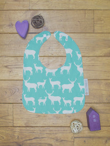 An organic Poco Bambino bib. The print is turquoise with a deer elk design.