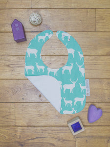 An organic Poco Bambino bib. The print is turquoise with a deer elk design. One corner is folded up to show the organic cotton and bamboo terry reverse