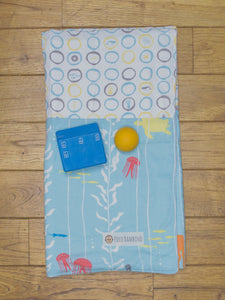 An organic Poco Bambino blanket. The print is blue, yellow and grey with a sea creatures design.