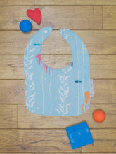 Load image into Gallery viewer, An organic Poco Bambino bib. The print is an under the sea design.