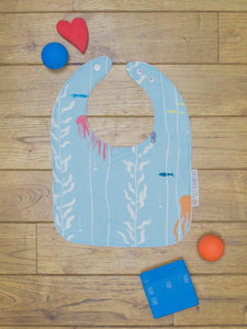 An organic Poco Bambino bib. The print is an under the sea design.