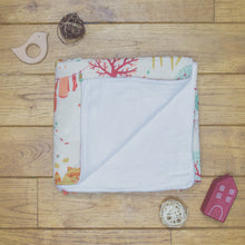 Load image into Gallery viewer, An organic Poco Bambino blanket. The print is the laundry day design. One corner is folded up to show the organic cotton and bamboo fleece reverse