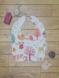 An organic Poco Bambino bib. The print is a forest laundry day design.