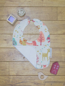 An organic Poco Bambino bib. The print is a forest laundry day design. One corner is folded up to show the organic cotton and bamboo terry reverse