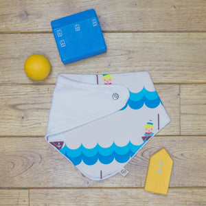 An organic Poco Bambino dribble bib. The print is a sailor design with sailors on little boats. One corner is folded up to show the organic cotton and bamboo terry reverse
