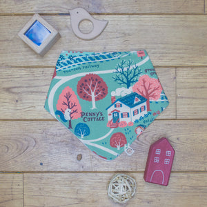 An organic Poco Bambino dribble bib. The print is an autumnal cottage in the woods design.