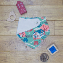 Load image into Gallery viewer, An organic Poco Bambino dribble bib. The print is an autumnal cottage in the woods design. One corner is folded up to show the organic cotton and bamboo terry reverse