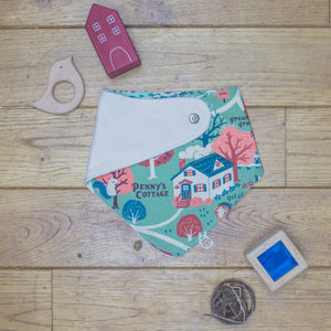 An organic Poco Bambino dribble bib. The print is an autumnal cottage in the woods design. One corner is folded up to show the organic cotton and bamboo terry reverse