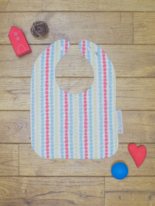 An organic Poco Bambino bib. The print is a multicoloured dots design.