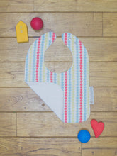 Load image into Gallery viewer, An organic Poco Bambino bib. The print is a multicoloured dots design. One corner is folded up to show the organic cotton and bamboo terry reverse