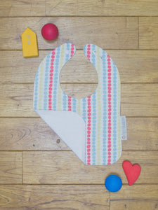 An organic Poco Bambino bib. The print is a multicoloured dots design. One corner is folded up to show the organic cotton and bamboo terry reverse