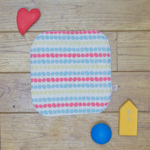 An Organic Poco Bambino reusable wash cloth / wipe in a multicoloured dots print.