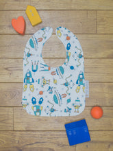 Load image into Gallery viewer, An organic Poco Bambino bib. The print is a robots and space rockets design.
