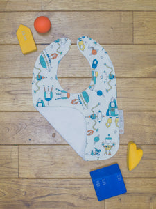 An organic Poco Bambino bib. The print is a robots and space rockets design. One corner is folded up to show the organic cotton and bamboo terry reverse
