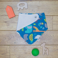 Load image into Gallery viewer, An organic Poco Bambino dribble bib. The print is a jungle animal design. One corner is folded up to show the organic cotton and bamboo terry reverse