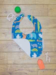An organic Poco Bambino bib. The print is jungle animals design. One corner is folded up to show the organic cotton and bamboo terry reverse