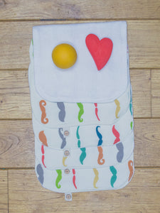 A set of 5 Organic Poco Bambino reusable wash cloths / wipes in a rainbow mustaches print. The top wipe is folded down to show the soft bamboo terry reverse.