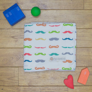 An organic Poco Bambino blanket. The print is a rainbow mustaches design.