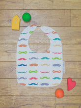 Load image into Gallery viewer, An organic Poco Bambino bib. The print is a rainbow mustache design. One corner is folded up to show the organic cotton and bamboo terry reverse