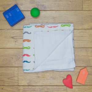 An organic Poco Bambino blanket. The print is a rainbow mustaches design. One corner is folded up to show the organic cotton and bamboo fleece reverse