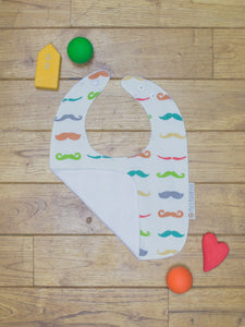 An organic Poco Bambino bib. The print is a rainbow mustache design. One corner is folded up to show the organic cotton and bamboo terry reverse